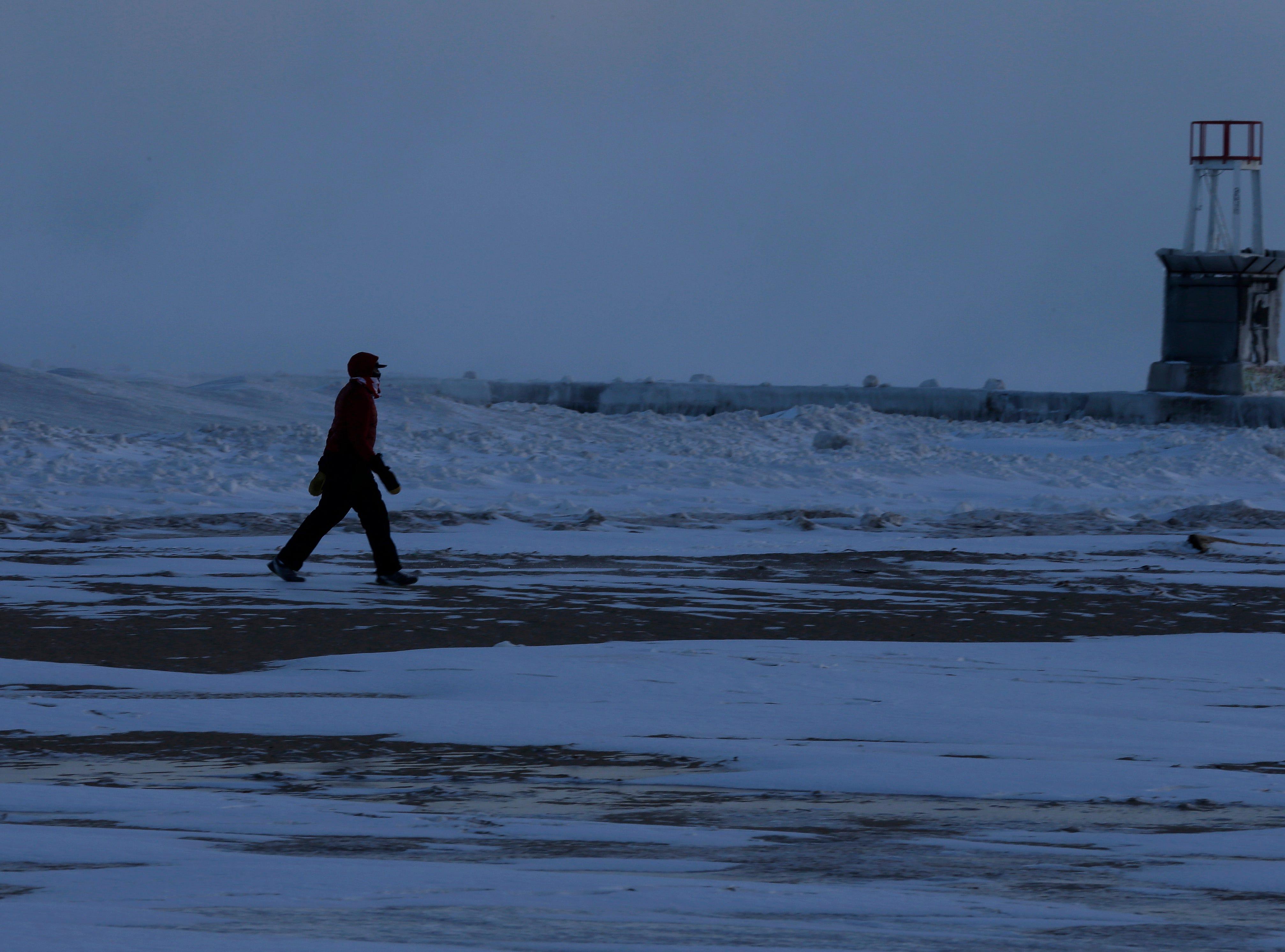 Un hombre camina a lo largo de la orilla del lago Michigan, el miércoles 30 de enero de 2019, en Chicago.