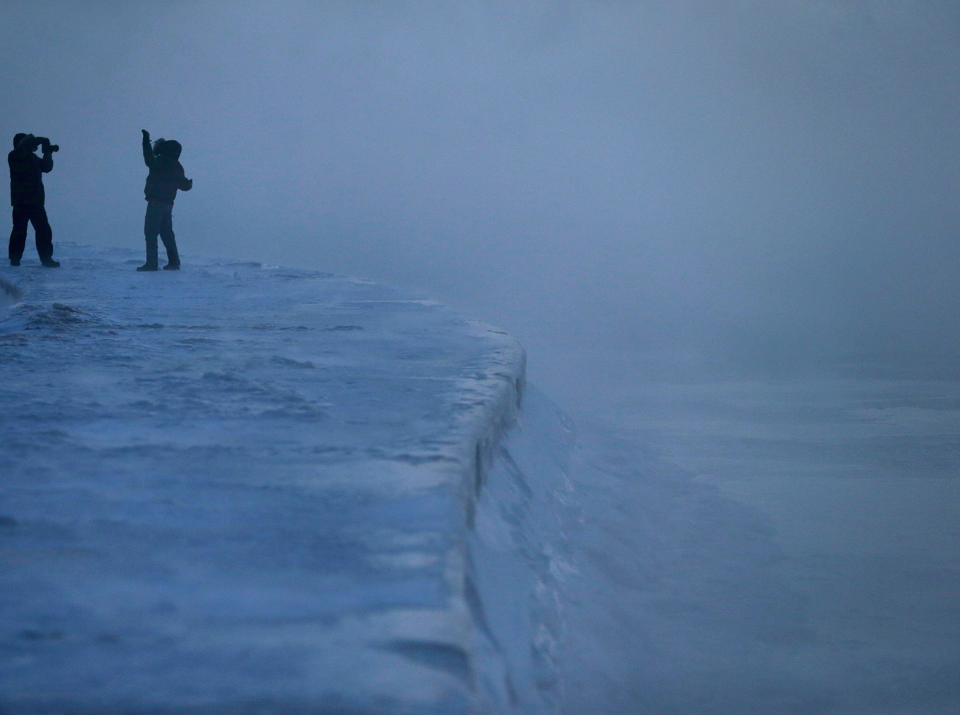 Un hombre posa para una foto mientras el hielo se forma a lo largo de la orilla del lago Michigan, el miércoles 30 de enero de 2019, en Chicago.