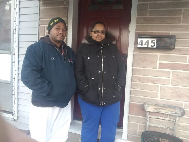 Eil and Julissa Flores stand in front of their home at 445 North Sixth Street, which was damaged by water from a fire hydrant on January 30, 2018.
