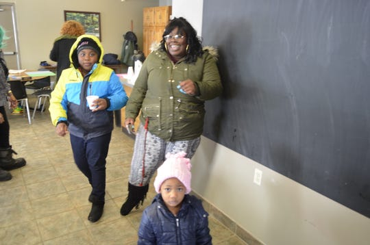 Port Huron mother Dionne Williams, center, cooked meals for distribution during a day of sub-zero temperatures on Jan. 30, 2019, She stands with her children Mackenzie Williams and Zoyie Williams at a warming center at Huron Village Community Center in Port Huron.