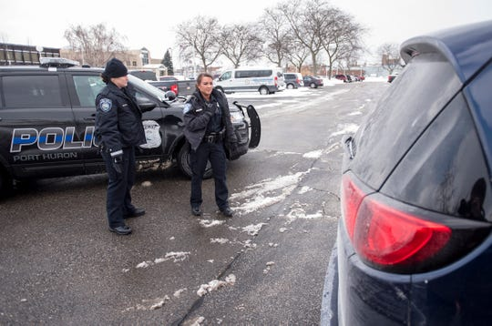 Port Huron Police Officer Adrianne Mynsberge, left, watches Ashley Marcano run a license plate while on patrol Tuesday, Jan. 29, 2019 in Port Huron.