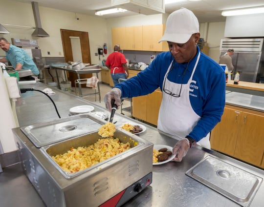 The Center of Port Huron volunteer David Hill serves a plate of breakfast Wednesday, Jan. 30, 2019 at  the center inside First Congregational Church.