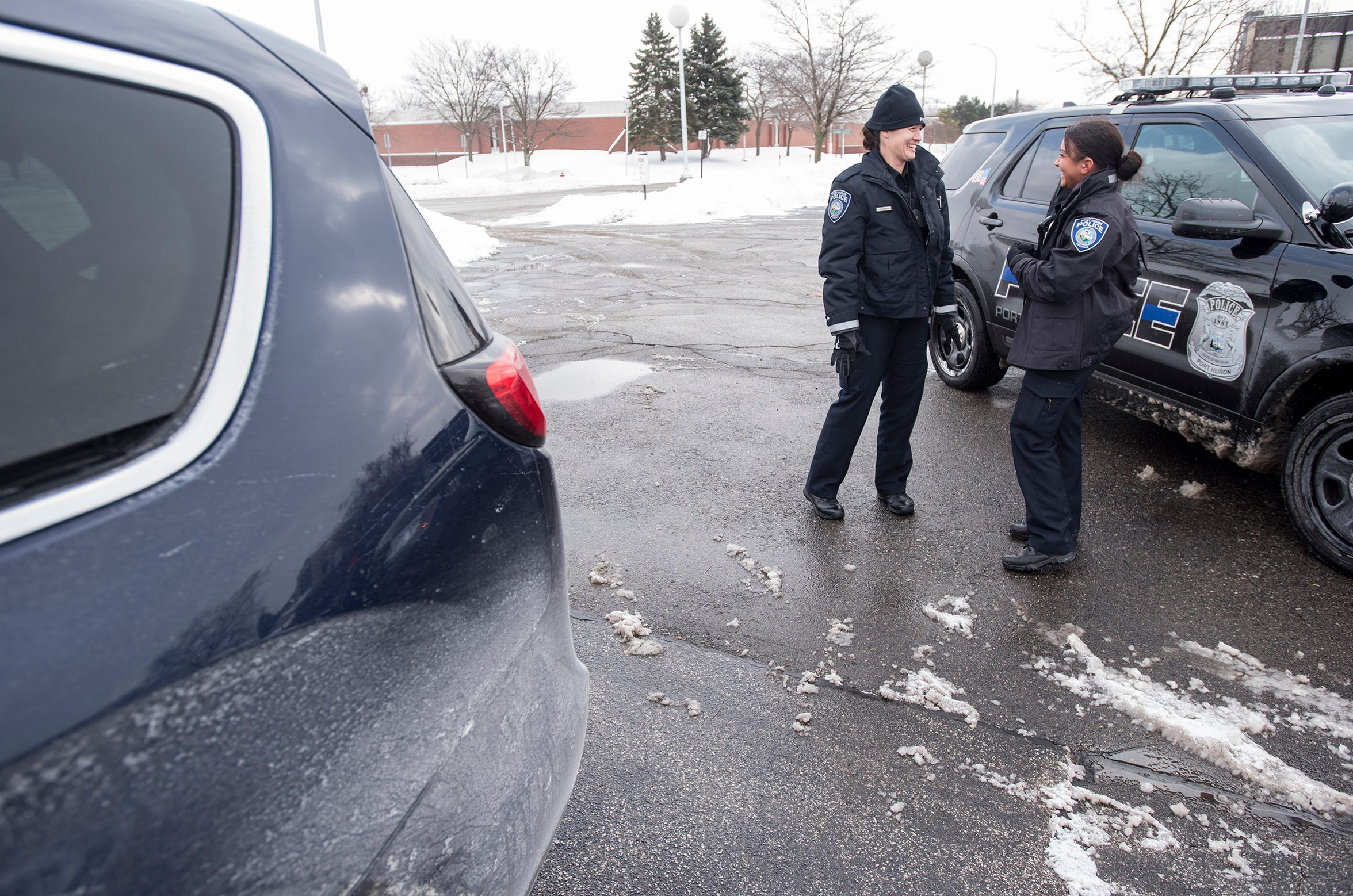 Port Huron Police Officers Adrianne Mynsberge, left, and Ashley Marcano talk while waiting to run a license plate on patrol Tuesday, Jan. 29, 2019, in Port Huron. Mysnberge has been with the department for 13 years, and Marcano just two months.