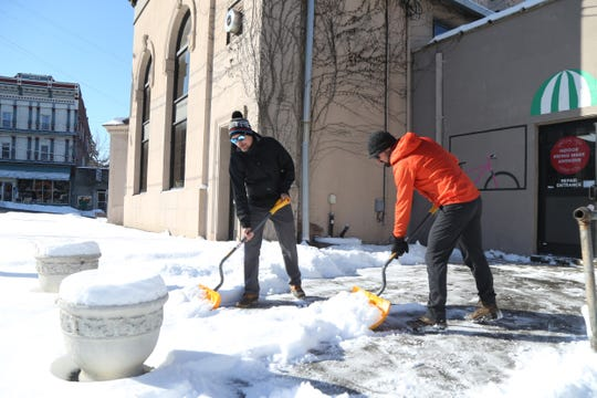 From left, Ed Madden and Mario Centuori clear the snow from the front of Wheel and Heel Bicycle Store in the Village of Wappingers Falls on January 30, 2019.
