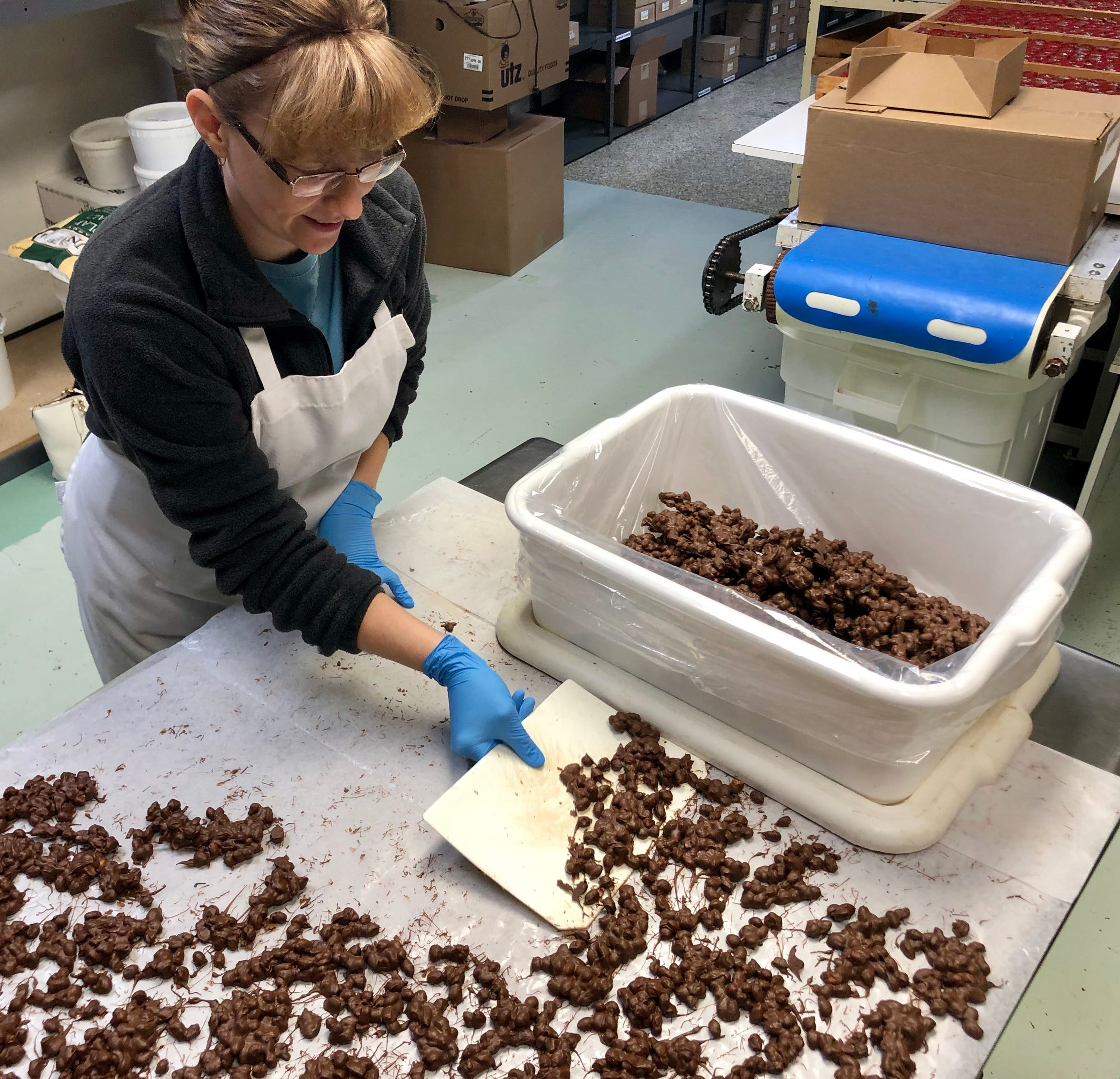 Jenny Nagy, an employee for Olympia Candy Kitchen, scoops up finished peanut clusters the morning of Thursday, Jan. 24, 2019. The candy store is one of three others that have been operating in downtown Chambersburg for more than 100 years.