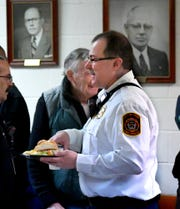 Retiring Chief David Michaels walks past York City Fire Department members and photos of past company presidents during a luncheon for him at Vigilant Fire Company Wednesday, Jan. 30, 2019. Michaels has been with the York City Fire Department for nearly 29 years. Bill Kalina photo