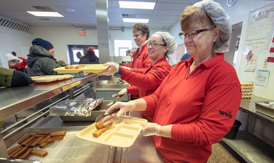 Gayle Hensel, right, loads french toast on a serving line for clients of Our Daily Bread. Hensel works at the White Street Weis. Diners enjoyed a hot meal while temperatures outside were in the single digits.