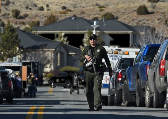 A armed deputy walks to a command truck at the scene of a standoff in Sparks on Tuesday Jan. 29, 3019.