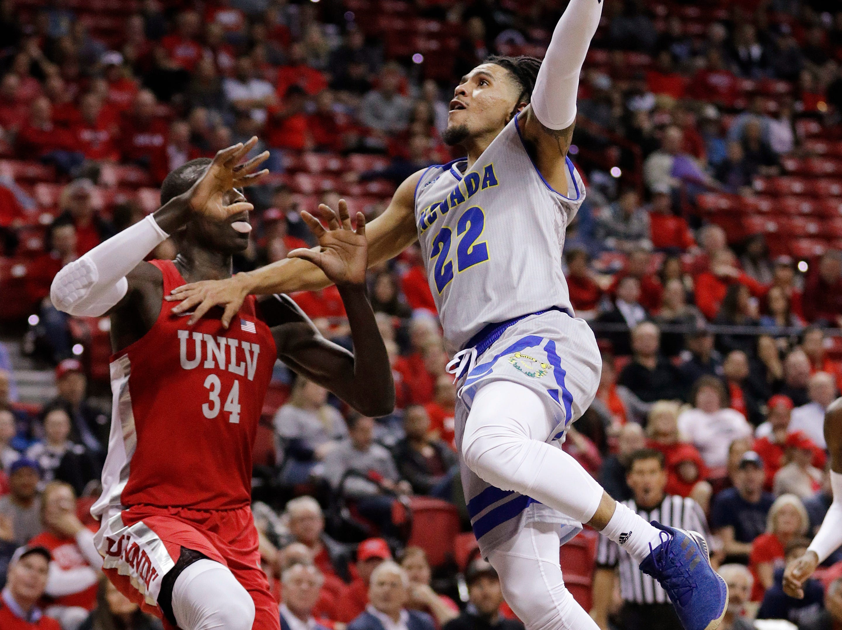 Nevada's Jazz Johnson shoots as UNLV's Cheikh Mbacke Diong defends during the second half of an NCAA college basketball game Tuesday, Jan. 29, 2019, in Las Vegas. (AP Photo/John Locher)
