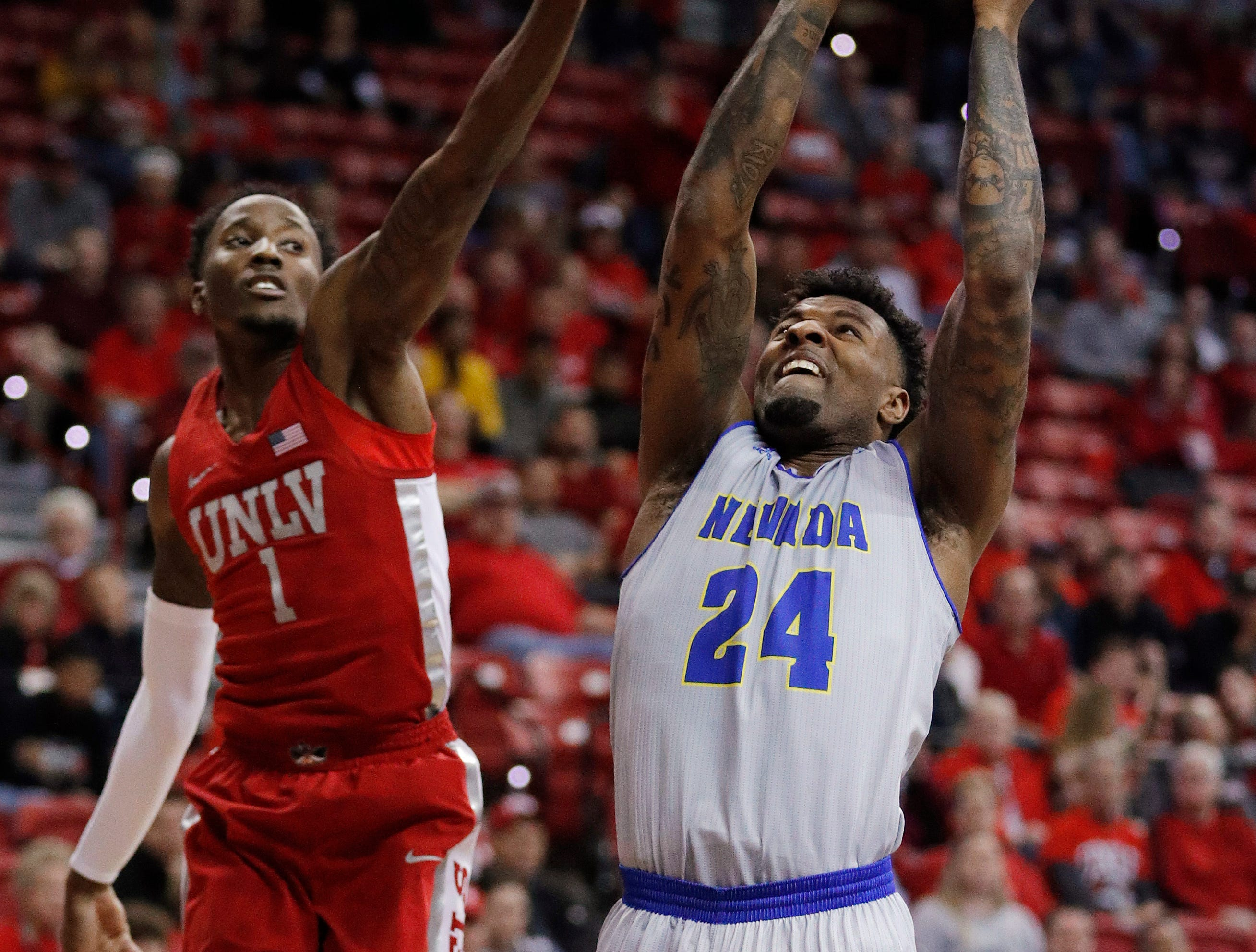 Nevada's Jordan Caroline (24) shoots as UNLV's Kris Clyburn defends during the second half of an NCAA college basketball game Tuesday, Jan. 29, 2019, in Las Vegas. Nevada won 87-70. (AP Photo/John Locher)