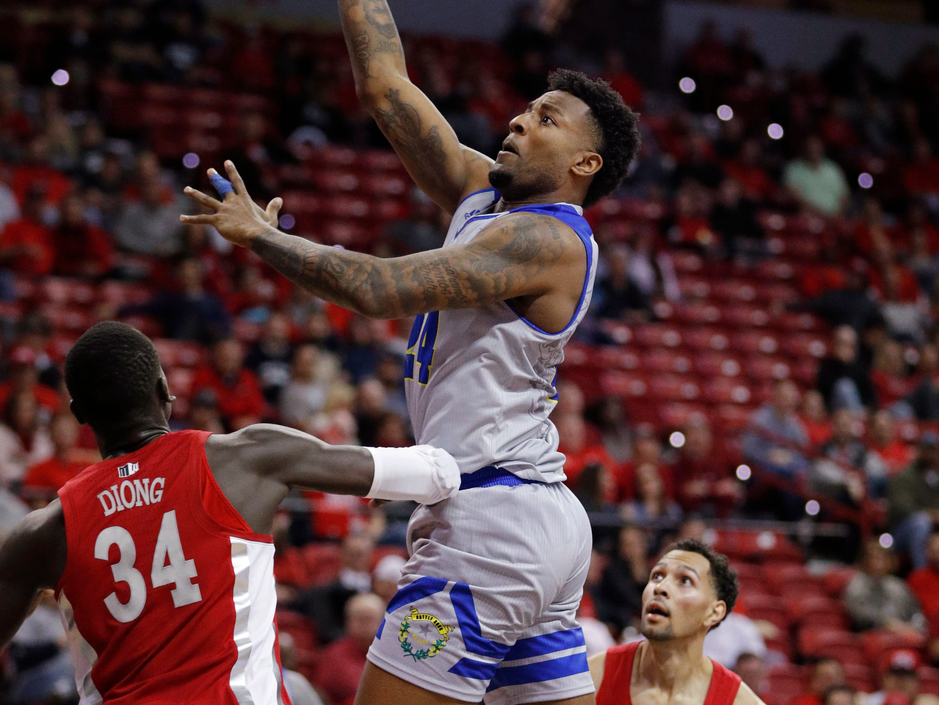 Nevada's Jordan Caroline shoots over UNLV's Cheikh Mbacke Diong during the second half of an NCAA college basketball game Tuesday, Jan. 29, 2019, in Las Vegas. (AP Photo/John Locher)