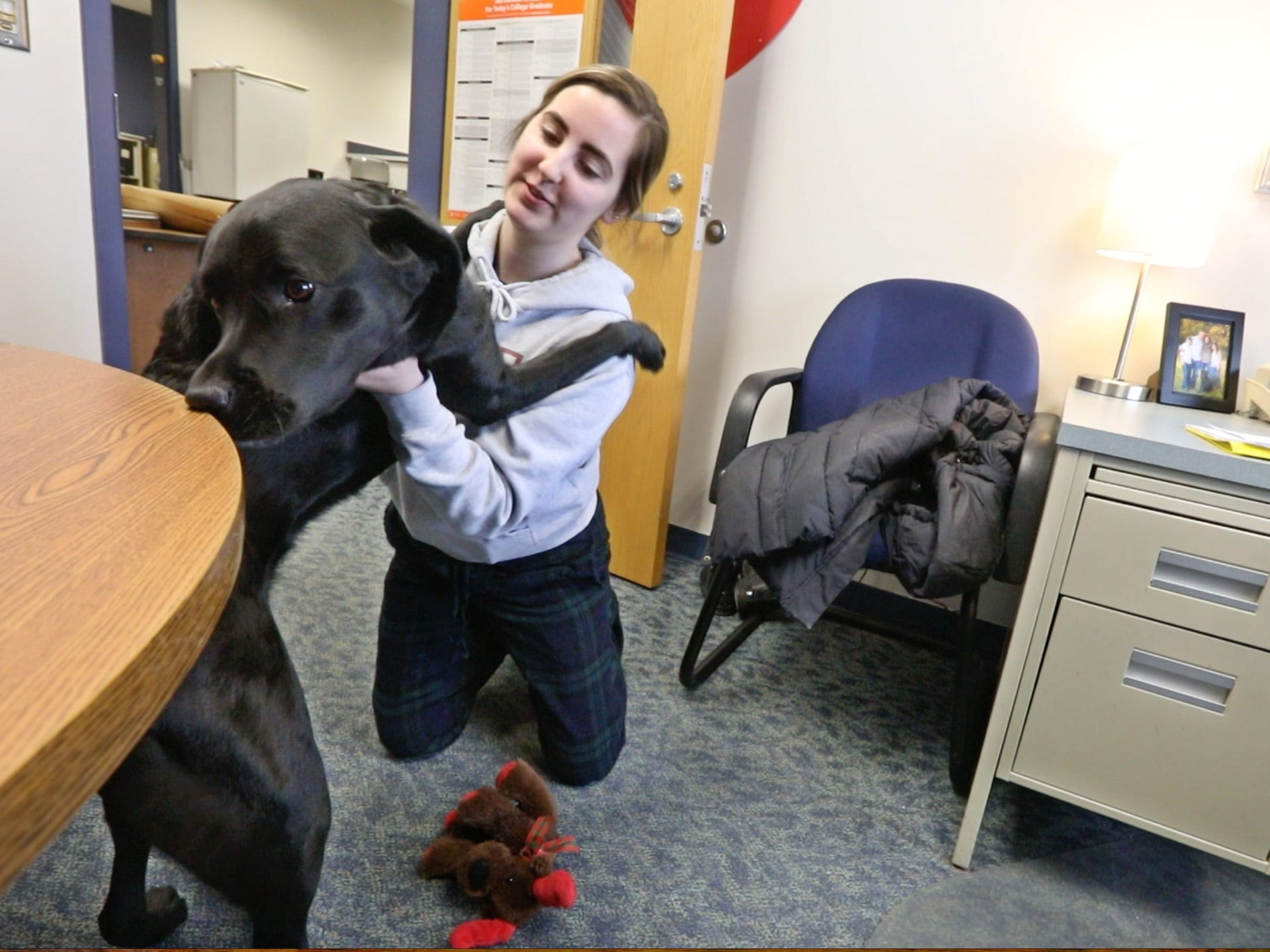 Breanna Tamburello, 17, a senior, visits with Ruby, a 4-year-old black Labrador retriever who is the new therapy dog at Spencerport High School, on Tuesday, Jan. 29, 2019.