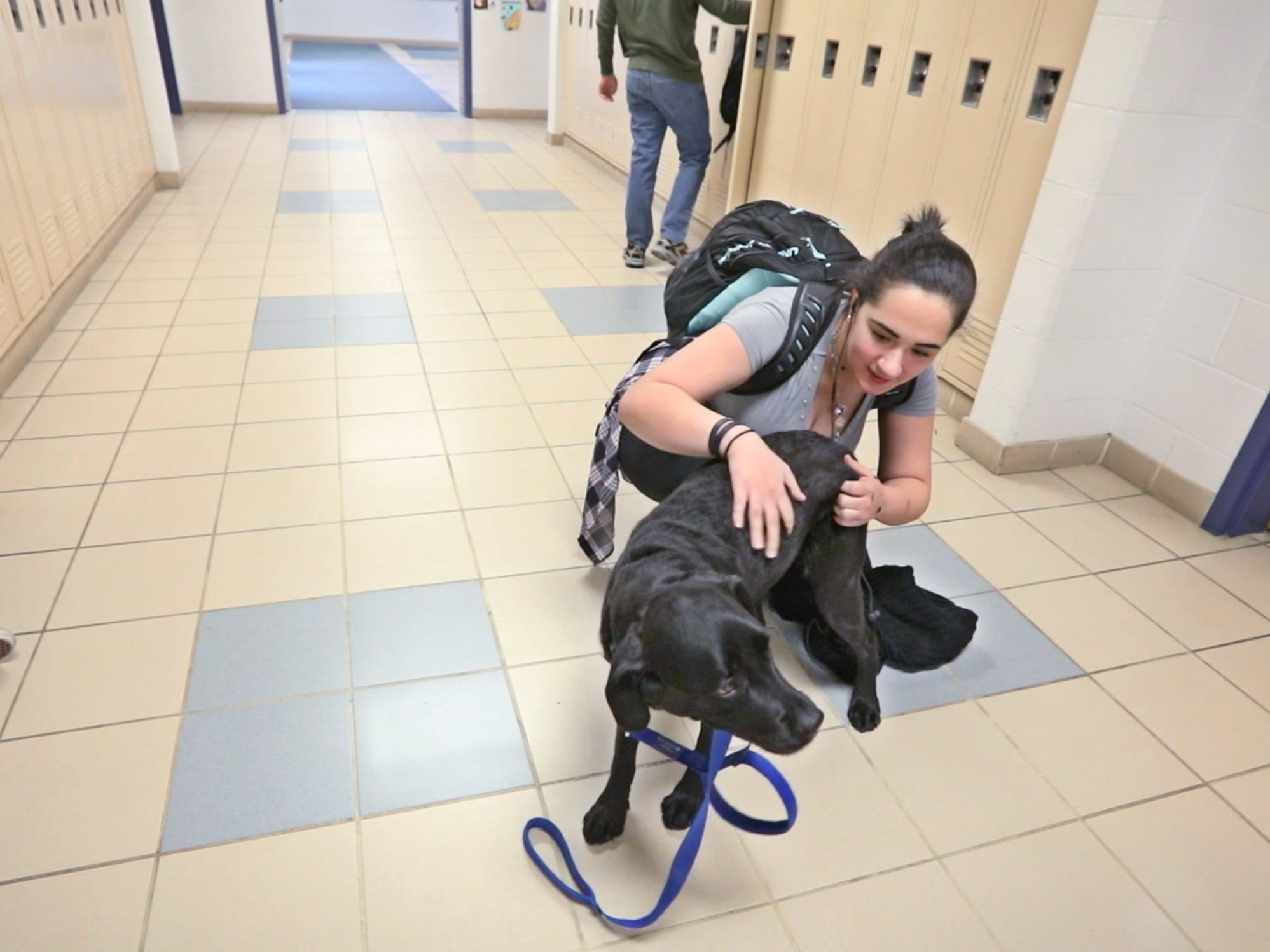 Jayanna McAfee, a junior at Spencerport High, visits with Ruby, a 4-year-old black Lab who is the new therapy dog at Spencerport High School, on Tuesday, Jan. 29, 2019.
