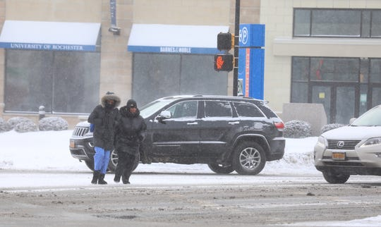 Pedestrians are bundled up against cold as they cross Elmwood at Mt. Hope Avenue.
