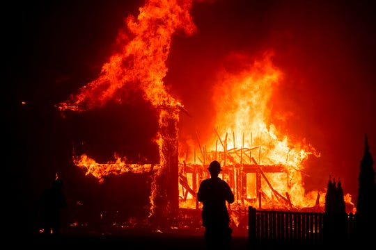 In this Nov. 8, 2018, file photo, a home burns as the Camp Fire rages through Paradise, Calif.