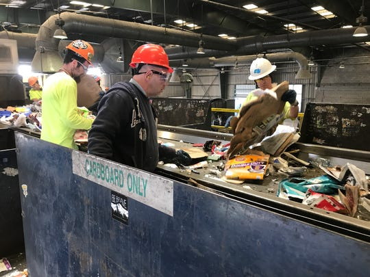 Workers separate garbage from recyclable materials at Redding's solid waste facility.