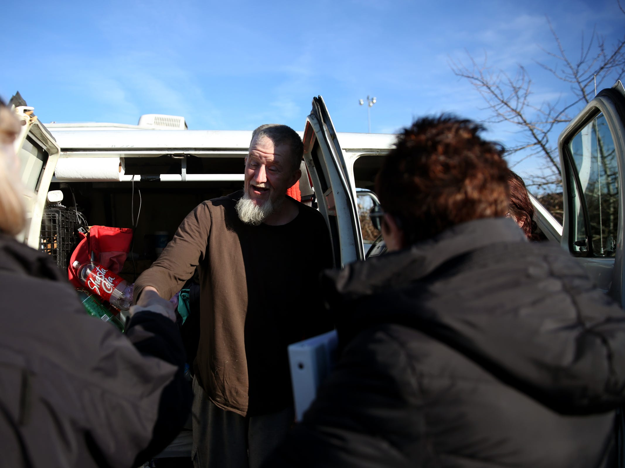 Aaron Webber, 43, greets volunteers Lorrie Walker, left, and Pamella Watson, outside the van he lives in with his girlfriend and dog during the annual Point-in-Time homeless count in Salem on Wednesday, Jan. 30, 2019. The number of people counted helps local programs qualify for federal funds to combat homelessness.