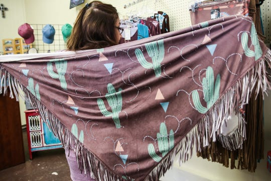 Patsy Cotton shows off a Western scarf Jan. 24, 2019, at her shop Serenity's Trading, 8 E. Concho Ave.