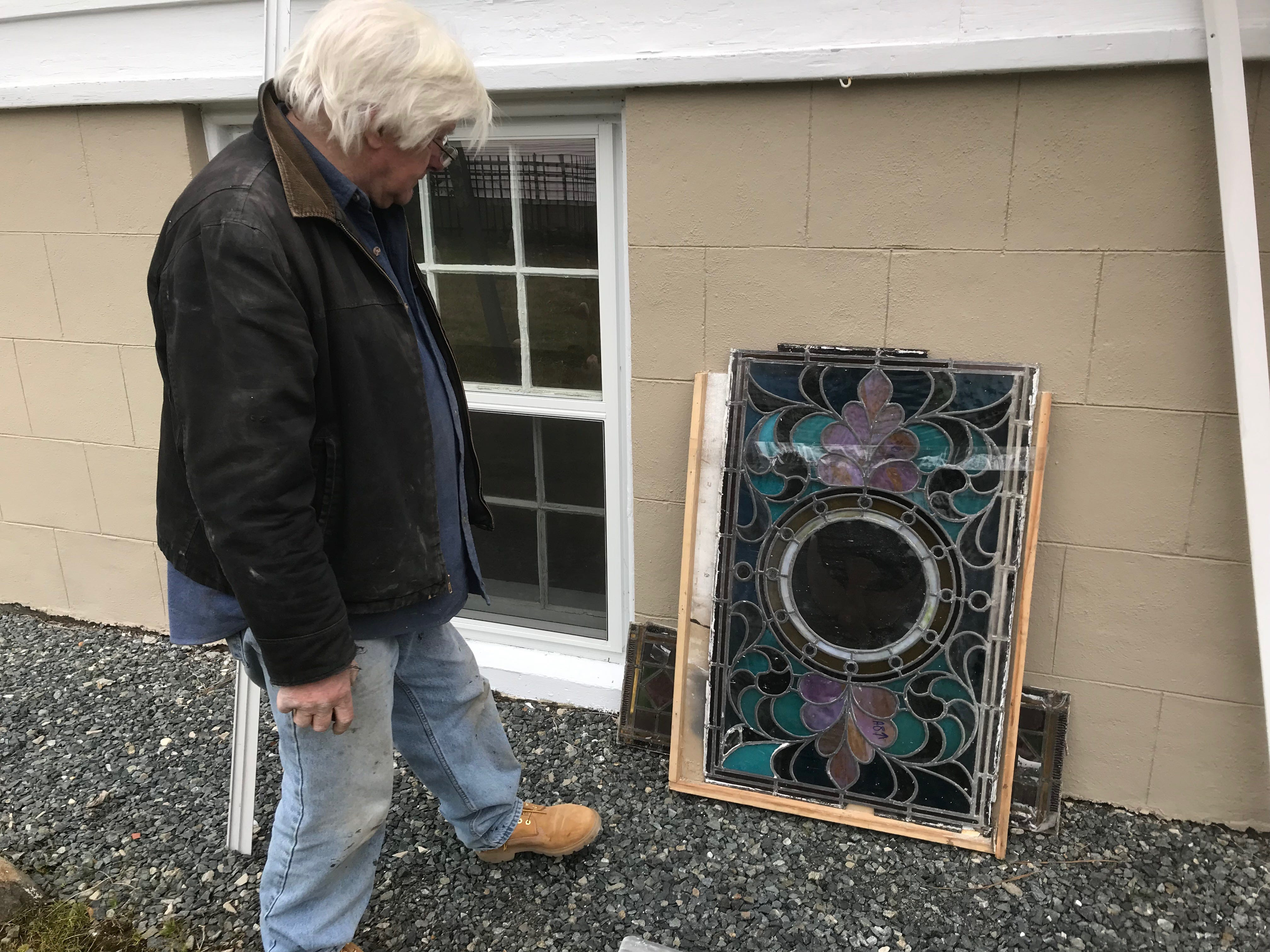 Michael Mezalick inspects a stained glass window he just removed from its frame at Historic Cokesbury Church in Onancock, VIrginia on Monday, Jan. 28, 2019. Mazalick is restoring the final three stained glass windows at the church — the end of a nearly 15-year-long restoration project.