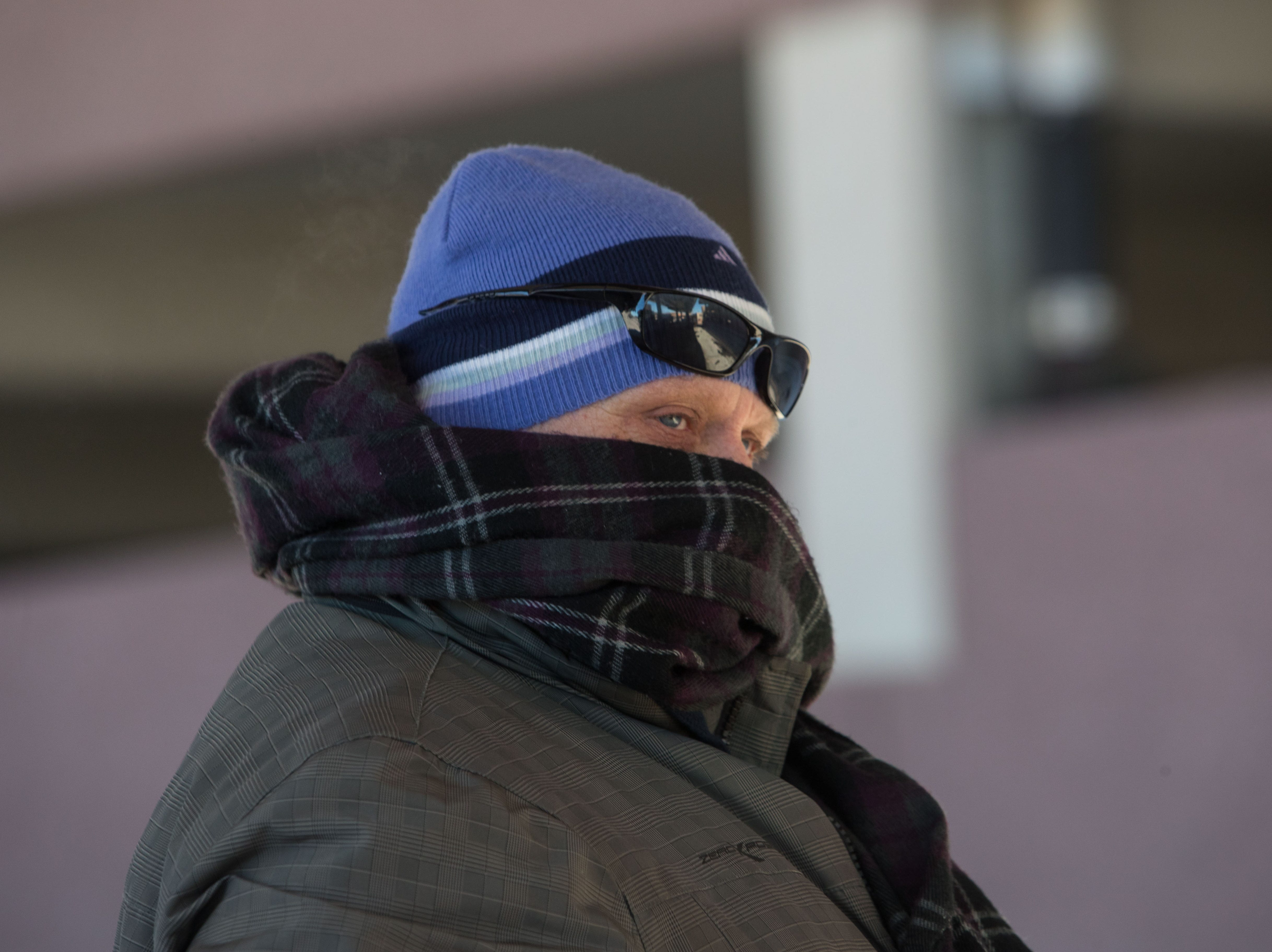 Sean Maher waits for his bus to arrive in downtown Sioux Falls, S.D., Wednesday, Jan. 30, 2019.