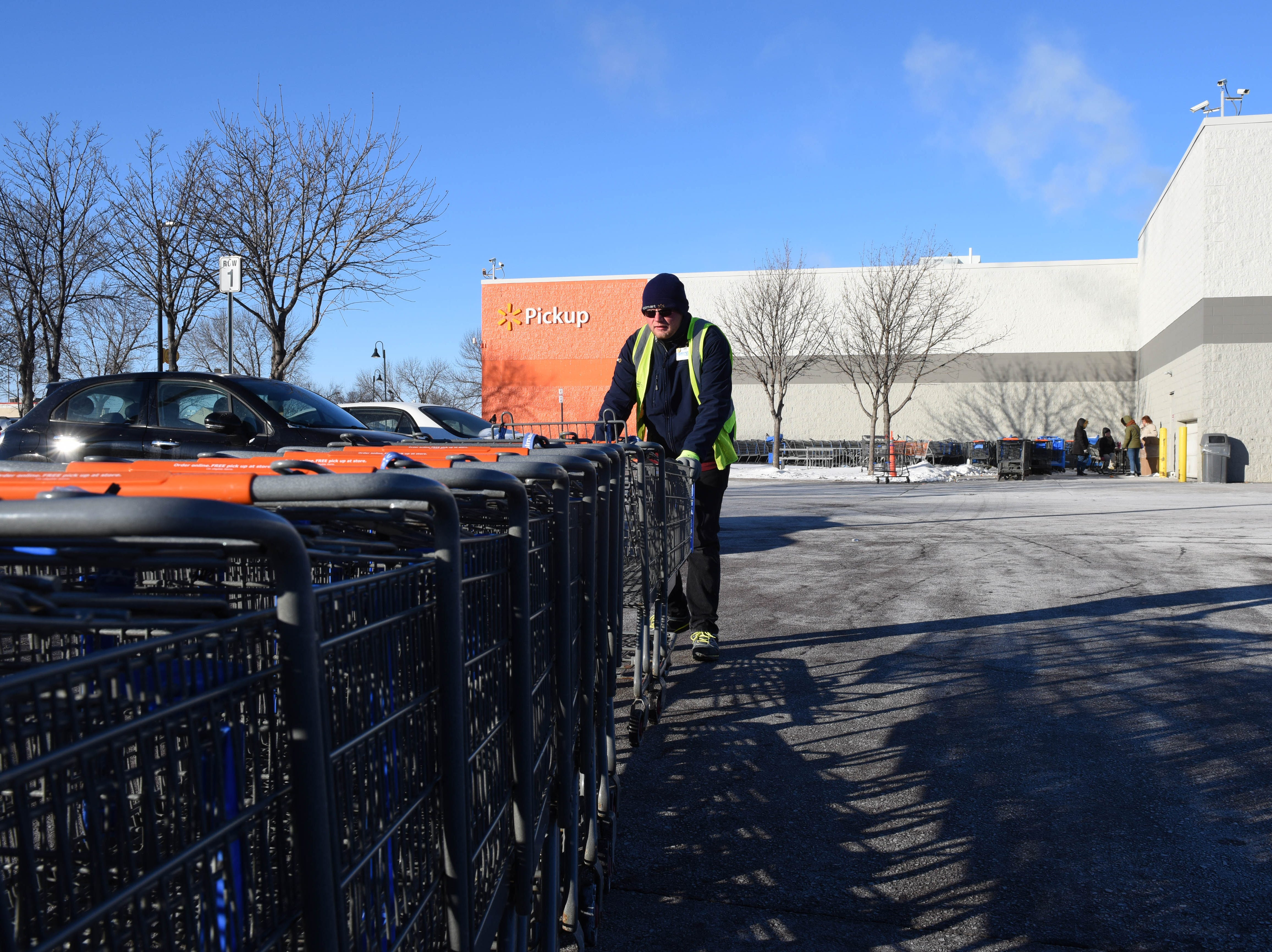 Luke Valeika gathers shopping carts at Walmart in Sioux Falls, S.D., Wednesday, Jan. 30, 2019.