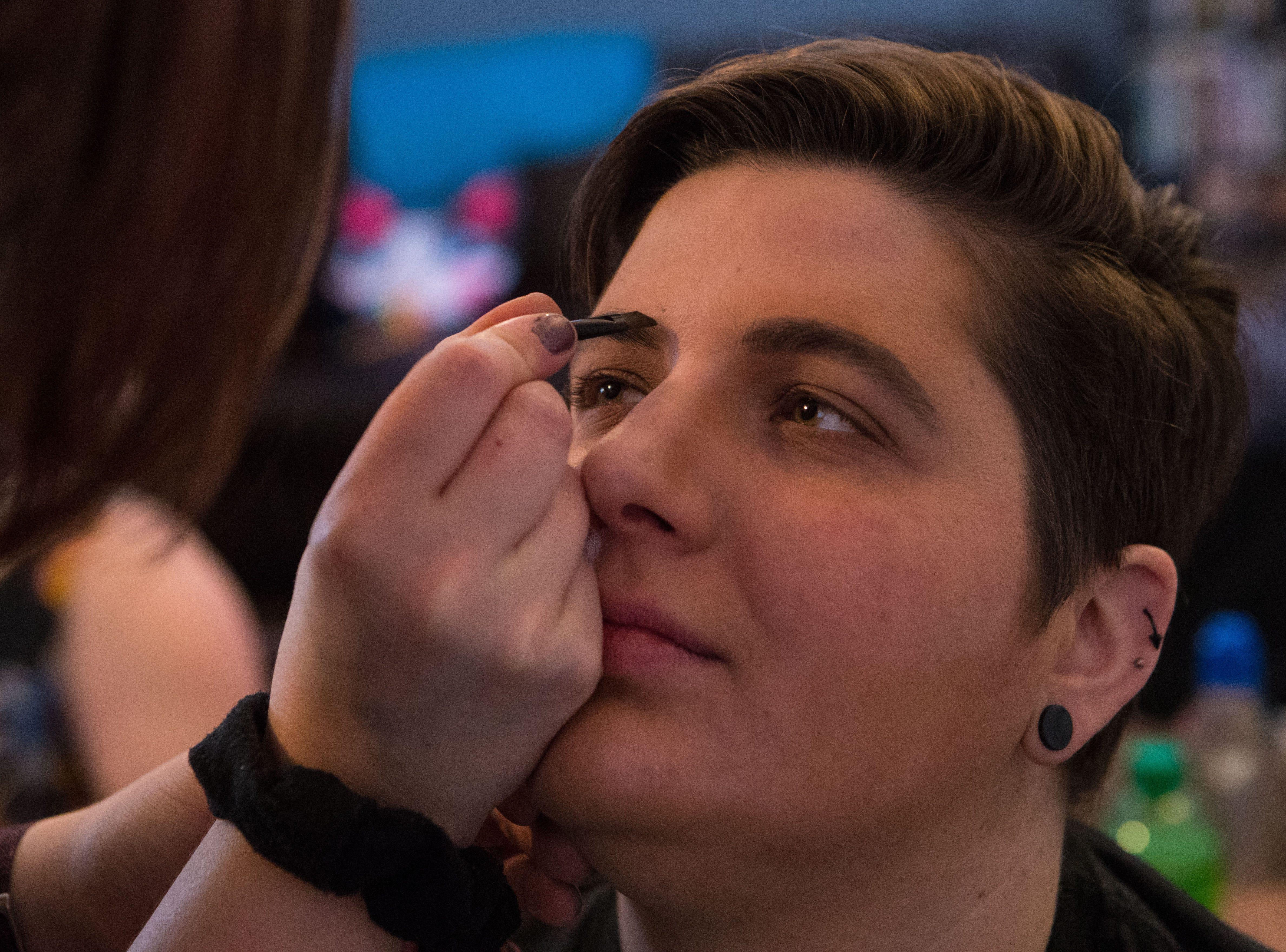 Christine Morgan does Katie Morgan's (drag name: Alex Feeliner) makeup during drag king rehearsal in Sioux Falls, S.D., Saturday, Jan. 26, 2019.