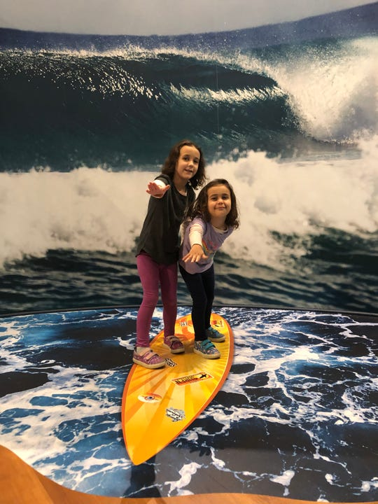 """Apollonia and Vivian Acevedo hang 10 at the Museum of Florida History's """"Surf's Up"""" exhibit."""