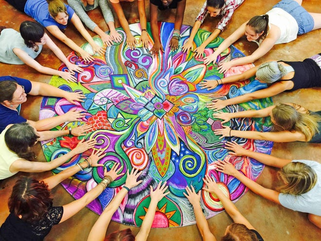 Students in the Art Therapy program at Florida State University reach out to their art creation.