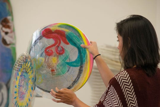 Theresa Sanchez, a master's degree candidate in art therapy at Florida State University, right, with artwork she created. Sanchez will be participating in the Bay County project.