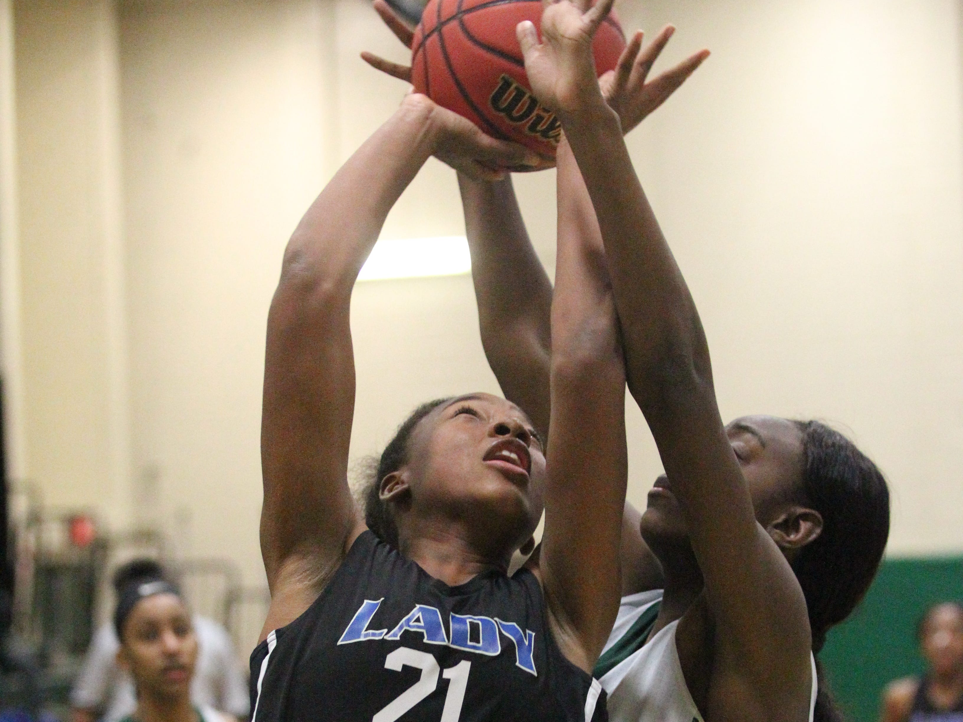 Godby's Essence Olivier goes up for a rebound against Lincoln's Ziare Reynolds as Lincoln's girls basketball team beat Godby 67-32 on Jan. 29, 2019.
