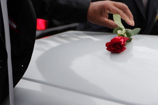 A red rose is placed on top of each casket as they are removed from the hearses. Eight of the lives lost during the fire at Dozier School for Boys in Marianna, Fla. in 1914, are in their final resting place at Boot Hill Cemetery on Wednesday, Jan. 30, 2019. The bodies were exhumed by a University of South Florida anthropologist over four years ago.