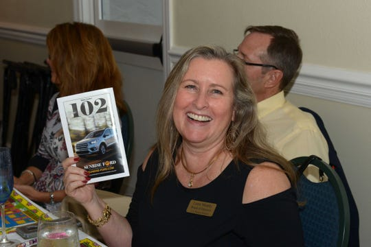 """Board of Director Laura Murphy wins an auction item at the """"Sunday in Key West"""" Luncheon & Auction benefit for the A.E. Backus Museum & Gallery in Fort Pierce."""