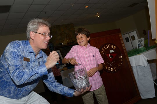 Connor Schindehette pulls the winning ticket for the solid gold, one Troy ounce Krugerrand coin from a vase held by Backus Museum Executive Director J. Marshall Adams.