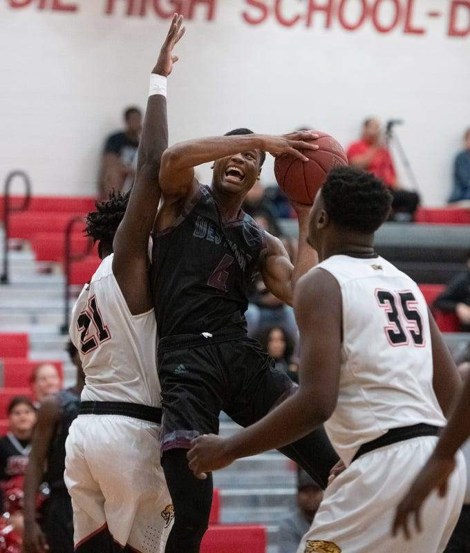 Fort Pierce Westwood's Willie Lewis (center) puts a shot up against Port St. Lucie's Ken Louis (left) and Daniel King in the first half of their game at Port St. Lucie High School on Tuesday, Jan. 29, 2019, in Port St. Lucie.