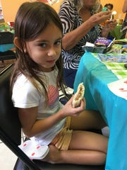 Alexa Bailey, 5, eats a peanut butter and jelly sandwich in a lunch provided by Treasure Coast Food Bank's Summer Meals program.