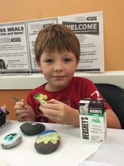 James Cowger, 8, enjoys a broccoli bite as part of lunch provided by Treasure Coast Food Bank's Summer Meals program.