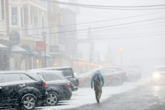 A man walks up Katonah Avenue in downtown Katonah during a brief snow squall Jan. 30, 2019.