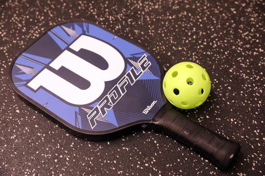 A pickleball paddle and wiffle ball at Solaris Sports Club in Yorktown Jan. 29 2019. Pickleball is a racquet sport that combines parts of tennis, badminton and ping pong.