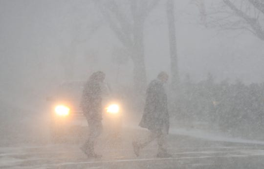 Pedestrians cross the Parkway in downtown Katonah during a brief snow squall Jan. 30, 2019.