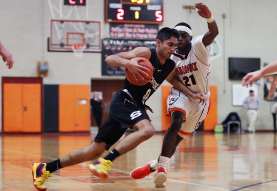 Scarsdale's  Jayshen Saigal (0) tries to drive around Mamaroneck's Tommy Martin (21) during boys basketball action at Mamaroneck High School Jan. 29, 2019. Mamaroneck won the game 58-53.