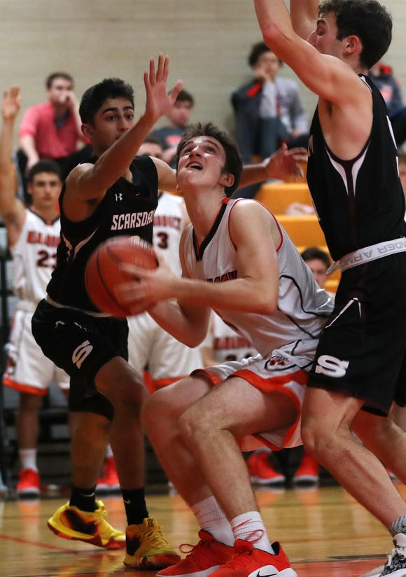 Mamaroneck's Gavin Zinghini (5) goes up for a shot in front of Scarsdale's Jayshen Saigal (0) and Eitan Altman (3) during boys basketball action at Mamaroneck High School Jan. 29, 2019. Mamaroneck won the game 58-53.