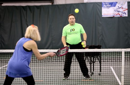 Lou Barlanti of Somers returns the ball to Geoffrey Jagdfeld, the director of tennis, during a pickleball lesson at Solaris Sports Club in Yorktown Jan. 29 2019. Pickleball is a racquet sport that combines parts of tennis, badminton and ping pong.