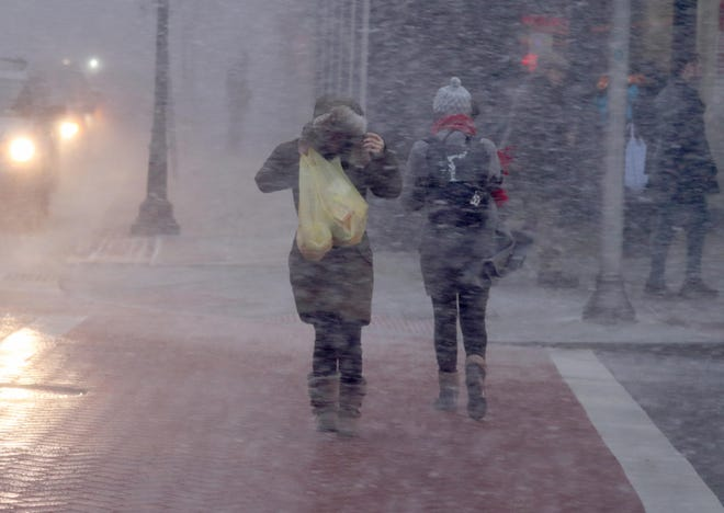 Pedestrians cross Mamaroneck Ave. in White Plains during a snow squall last month. The region's upcoming brush with winter weather won't amount to much, Accuweather meteorologist Paul Walker says.