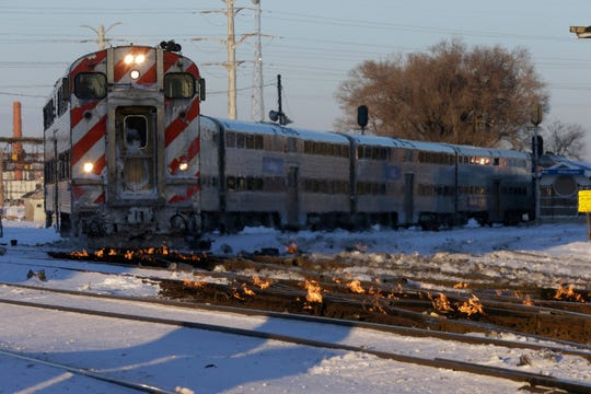 A metro train moves southbound to downtown Chicago as the gas-fired switch heater on the rails keeps the ice and snow off the switches near Metra Western Avenue station in Chicago, Tuesday, Jan. 29, 2019. Forecasters warn that the freezing weather Tuesday will get worse and could be life-threatening.