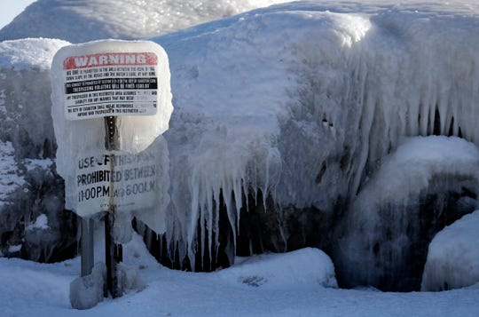 A warning sign is covered by ice at Clark Square park in Evanston, Ill., Wednesday, Jan. 30, 2019. A deadly arctic deep freeze enveloped the Midwest with record-breaking temperatures on Wednesday, triggering widespread closures of schools and businesses, and prompting the U.S. Postal Service to take the rare step of suspending mail delivery to a wide swath of the region.