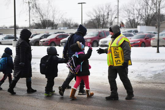 Terrin Haggerty, counselor at Susan B. Anthony Elementary School, helps students walk across the intersection, while on crosswalk duty for early dismissal in Sioux Falls, S.D., Tuesday, Jan. 29, 2019. Temperatures in the Dakotas and Minnesota dropped on Tuesday to as low as minus 27 (negative 33 degrees Celsius) with wind chills as cold as minus 59 (negative 51 degrees Celsius).