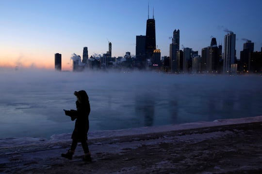 A person walks along the lakeshore, Wednesday, Jan. 30, 2019, in Chicago. A deadly arctic deep freeze enveloped the Midwest with record-breaking temperatures on Wednesday, triggering widespread closures of schools and businesses, and prompting the U.S. Postal Service to take the rare step of suspending mail delivery to a wide swath of the region.