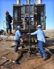 In this file photo, Justin Hughes, left, Randy Ramirez and Steven Wells, right, of Bridwell Oil Company, work in an injection well on the Bridwell River Ranch.