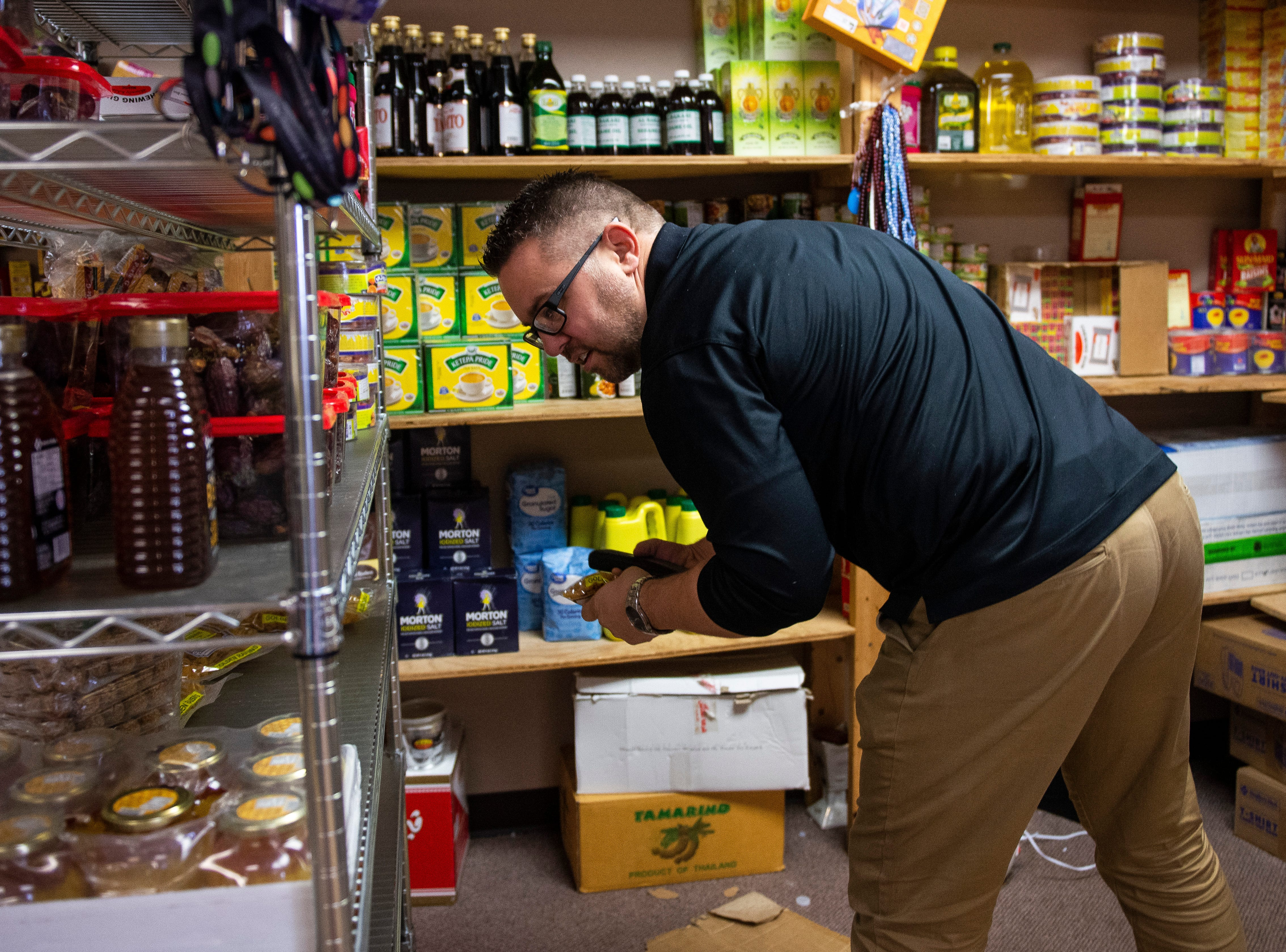 Kearny County Hospital CEO Benjamin Anderson shops at the African Shop, which stocks East African groceries and clothes. Anderson started buying tea, dates and olive oil at the African Store, slowly establishing a relationship with the staff and other customers.