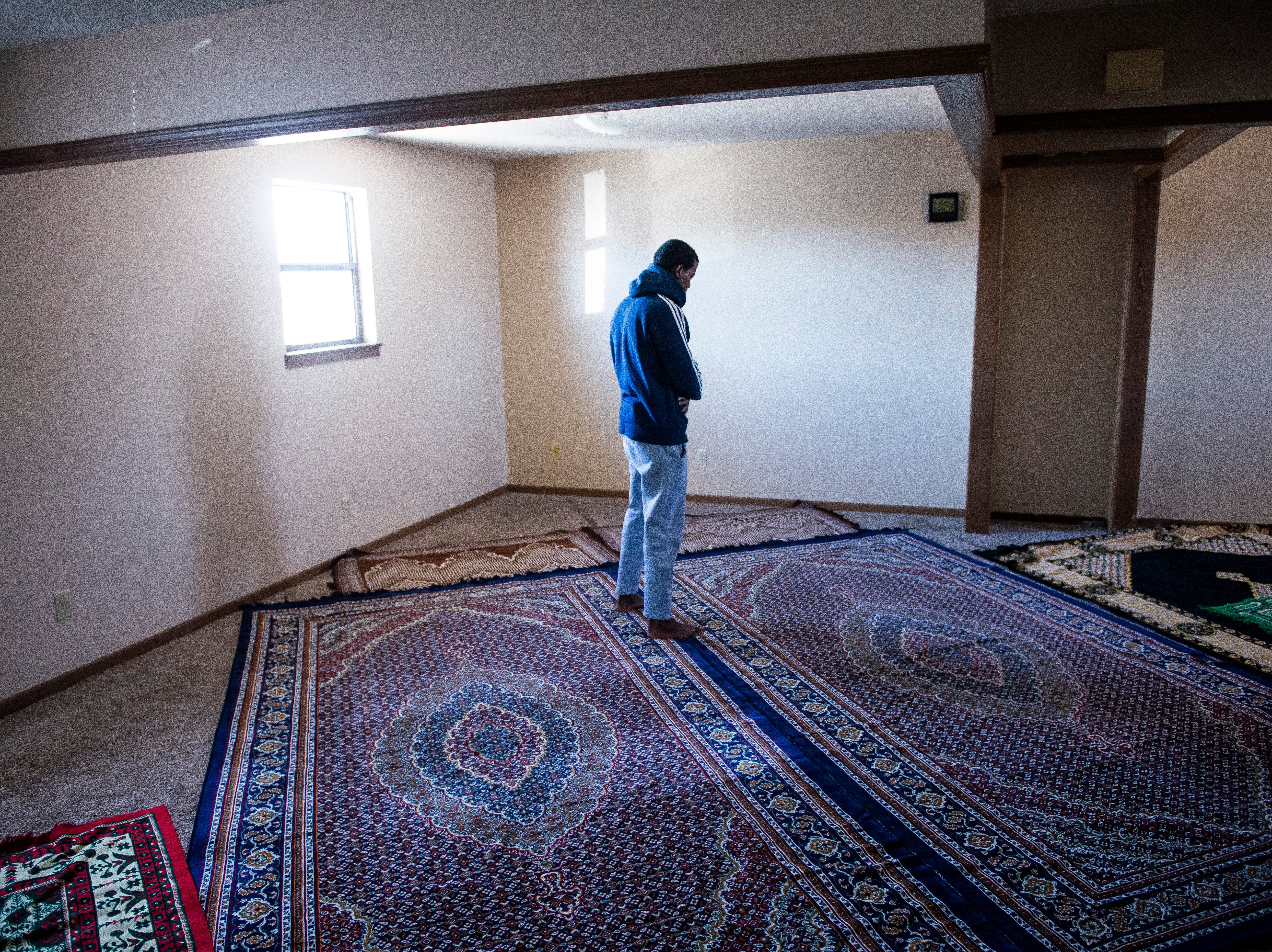 Abdulfeta Ahmed, 20, a refugee from Ethiopia, prays in an apartment that has been turned into a mosque at the Garden Spot Apartments Wednesday, Jan. 23, 2019.